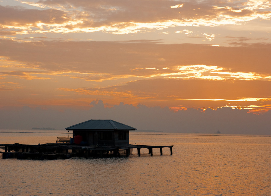 Photograph of a sunrise over a fishing platform in the Java Sea